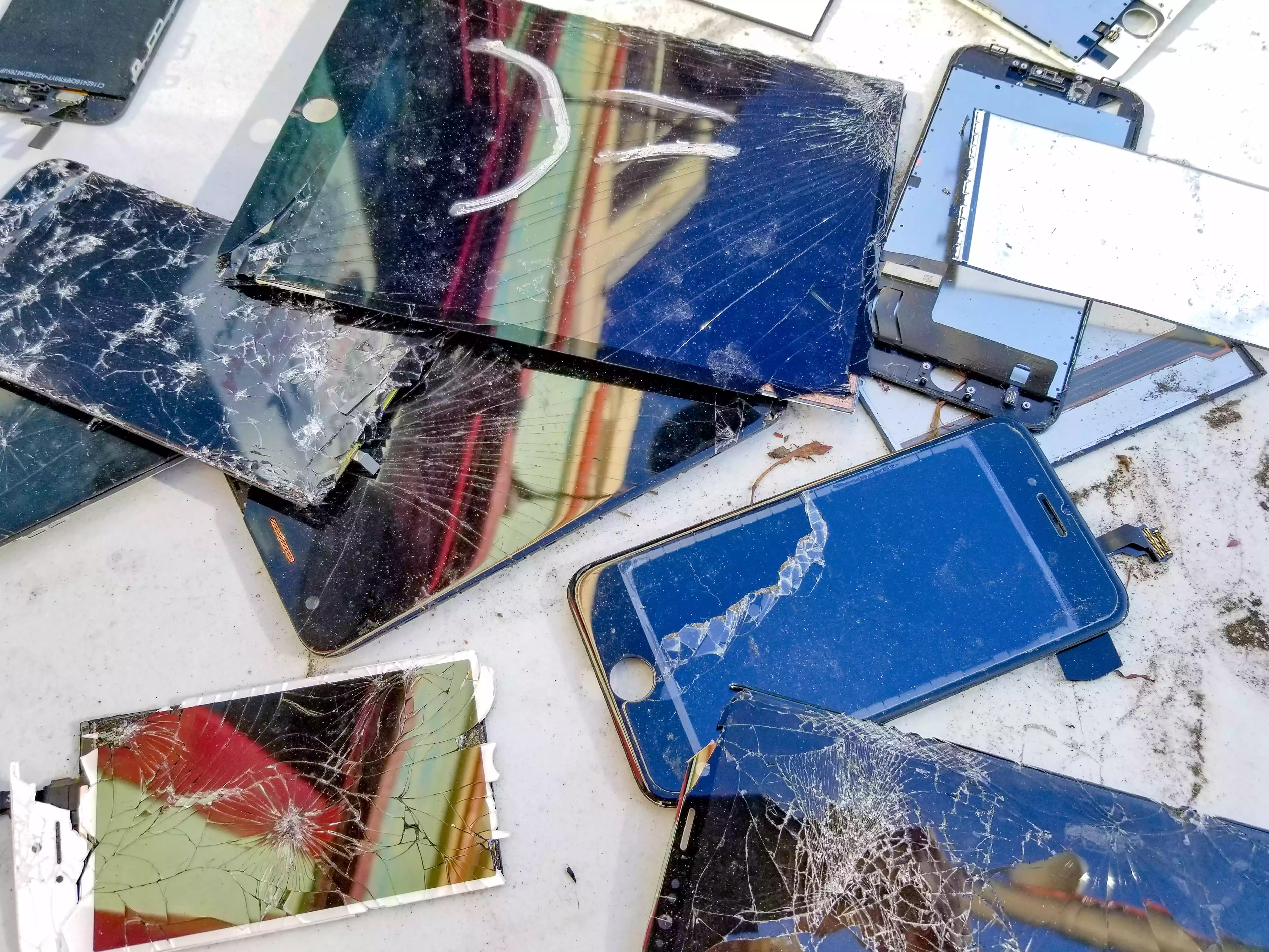 Several broken smartphones and tablets with cracked screens on a table.