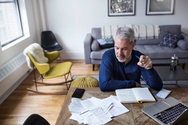 high angle view of mature man analyzing bills at table in home - focus on budgeting stock pictures, royalty-free photos & images