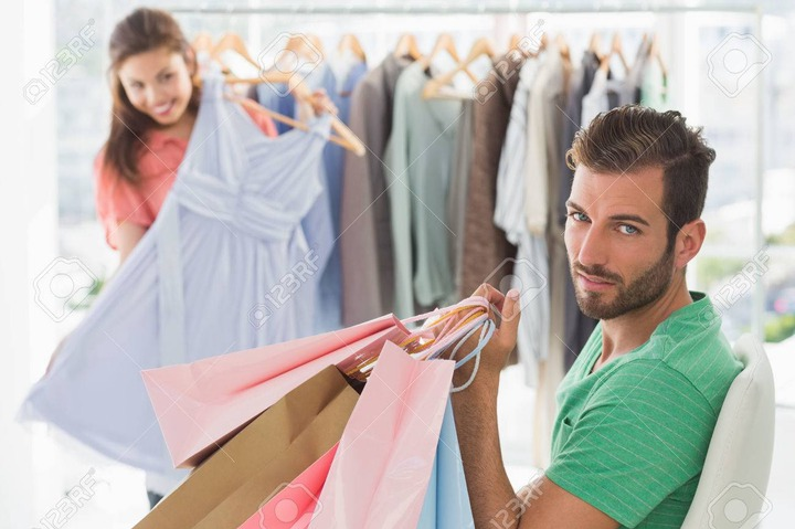 Bored Man Sitting With Shopping Bags While Woman By Clothes Rack In The  Background Stock Photo, Picture And Royalty Free Image. Image 27145268.