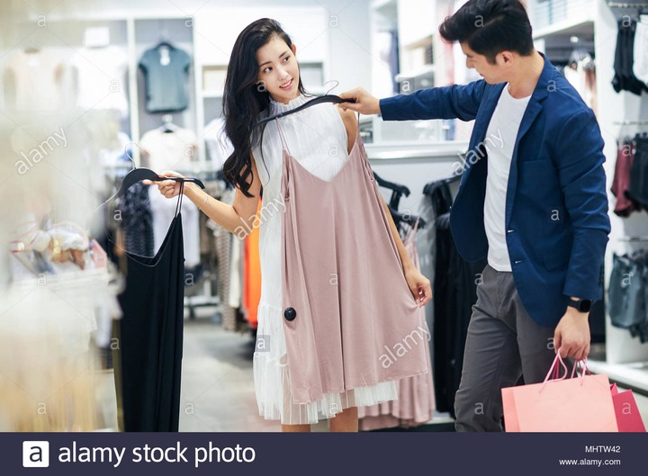 Young couples choose clothes clothing store Stock Photo - Alamy