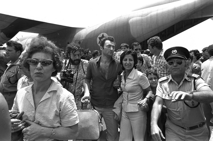 A policeman clears the way for rescued Air France hostages returning from Entebbe Airport on July 4 1976.