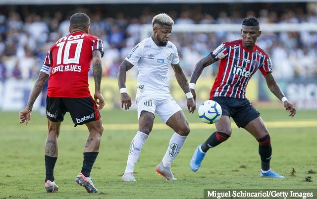 Marinho (C) of Santos vies the ball with Daniel Alves and Arboleda (R) of Sao Paulo during a match between Santos and Sao Paulo for the Brasileirao Series A 2019 at Vila Belmiro Stadium on...