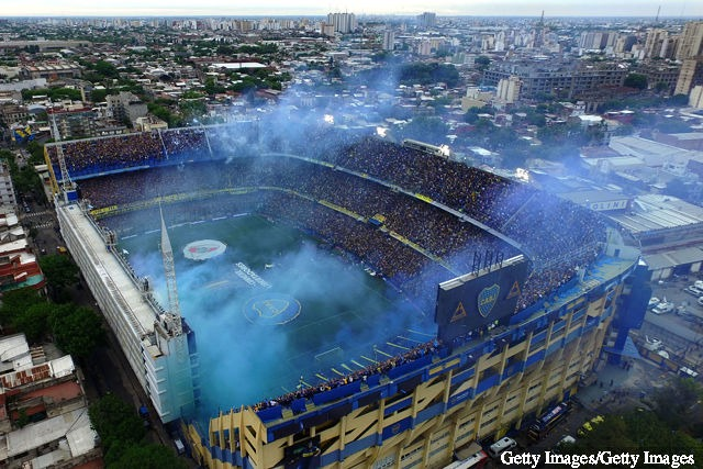 Smoke flares are seen as players walk onto the field before the first leg match between Boca Juniors and River Plate as part of the Finals of Copa CONMEBOL Libertadores 2018 at Estadio...