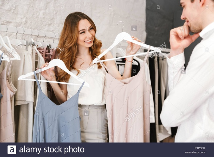 Attractive young couple shopping for clothes together at the clothing store  Stock Photo - Alamy
