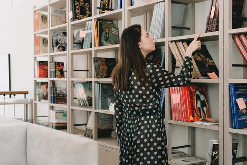 Young woman choosing book from bookshelf