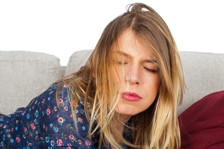 Tired unkempt woman on te couch. Picture of a tired unkempt woman lying on he couch at home stock photo