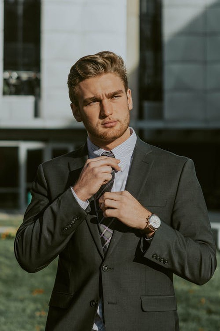Serious confident male entrepreneur wearing classy suit and wristwatch holding tie while thoughtfully looking away