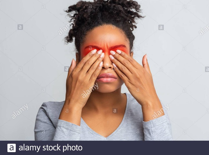 Black woman covering her eyes with palms, highlighted red zone, eye diseases  concept Stock Photo - Alamy