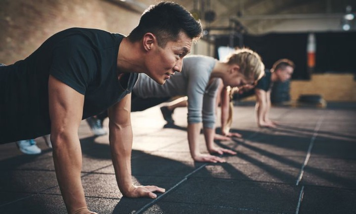 Workout class participants arrayed laterally along mat-covered floor, each simultaneously at apex of pushup motion
