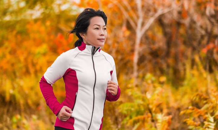 Woman in cool-weather running gear runs past an autumn-colored background of vegetation