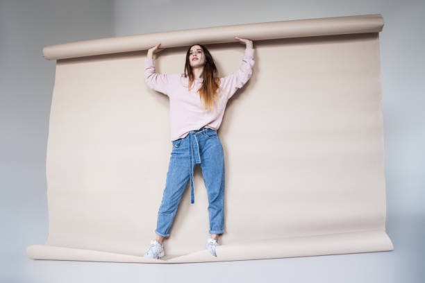 trendy female with huge roll of paper - big jeans for lady stock pictures, royalty-free photos & images