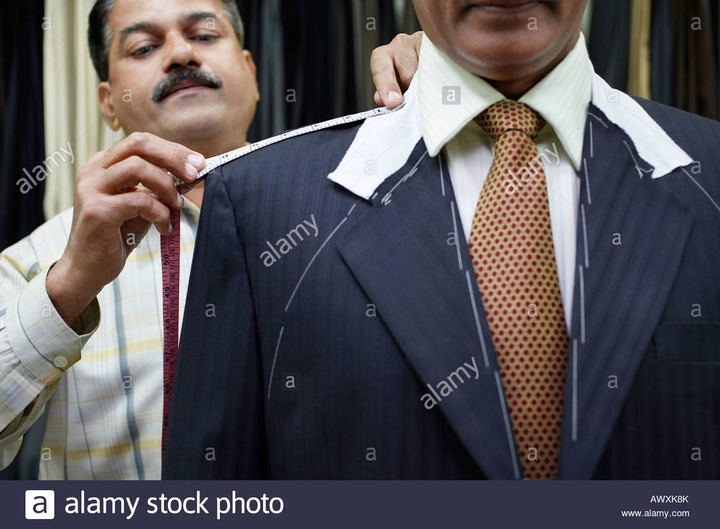 Tailor measuring business man with tape measure, close up Stock Photo -  Alamy