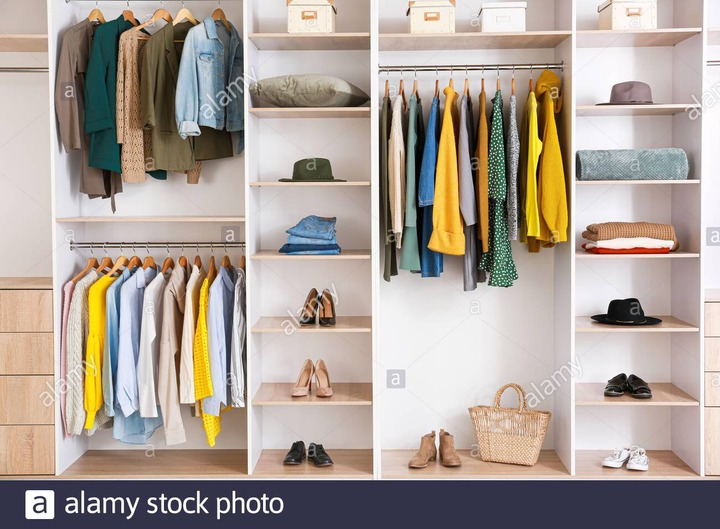 Big wardrobe with clothes in dressing room Stock Photo - Alamy