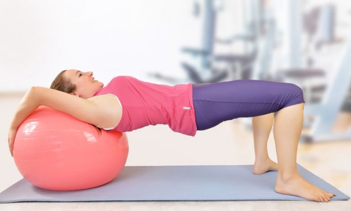 Woman in gym clothes facing upward, leaning back of her shoulders against large exercise ball, elevating torso horizontally