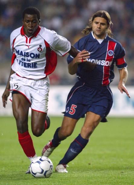 Le capitaine parisien Mauricio Pochettino est accroché par l'attaquant niçois Kaba Diawara, le 31 août 2002 aux Parc des Princes à Paris, lors du...